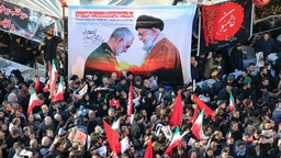 "Iranian mourners carry a picture of Iran's Supreme Leader Ayatollah Ali Khamenei (R) granting the Order of Zolfaghar, the highest military honour of Iran, to General Qasem Soleimani, during the latter's funeral procession in the capital Tehran on January 6, 2020. - Downtown Tehran was brought to a standstill as mourners flooded the Iranian capital to pay an emotional homage to Soleimani, the ""heroic"" general who spearheaded Iran's Middle East operations as commander of the Revolutionary Guards' Quds Force and was killed in a US drone strike on January 3 near Baghdad airport along with Iraqi paramilitary chief Abu Mahdi al-Muhandis and others."