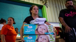 "A woman carries boxes of baby wipes she removed from a warehouse filled with supplies, including thousands of cases of water, believed to have been from when Hurricane Maria struck the island in 2017 in Ponce, Puerto Rico on January 18, 2020, after a powerful earthquake hit the island. - President Donald Trump on January 16 freed up emergency aid for Puerto Rico's recovery from a January 7 earthquake that caused widespread disruption and damage on the island. Trump's declaration of a major disaster in Puerto Rico makes federal funding available for repairs, temporary housing and low-cost loans ""to help individuals and business owners recover from the effects of the disaster,"" the White House said. (Photo by Ricardo ARDUENGO / AFP) (Photo by RICARDO ARDUENGO/AFP via Getty Images)"