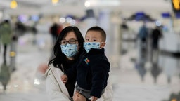 A woman and a child wearing protective masks walk toward check-in counters at Daxing international airport in Beijing on January 21, 2020.