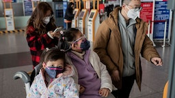 People travelling for the Lunar New Year wear protective masks as they head to the departure area at the Beijing Capital International Airport in Beijing on January 22, 2020.