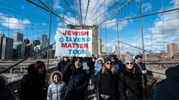 """MANHATTAN, NY - JANUARY 05: A young marcher walking across the Brooklyn Bridge carrying a handmade sign that says """"Jewish Lives Matter Too"""" with a Jewish star with the Brooklyn Bridge Arch and the Freedom Tower behind them. This was part of the effort to support the No Hate No Fear Jewish Solidarity March which started in Foley Square in the Manhattan borough of New York and walked across the Brooklyn Bridge to raise awareness of no tolerance for violence against Jewish people. The March was held on January 01, 2020, USA."""