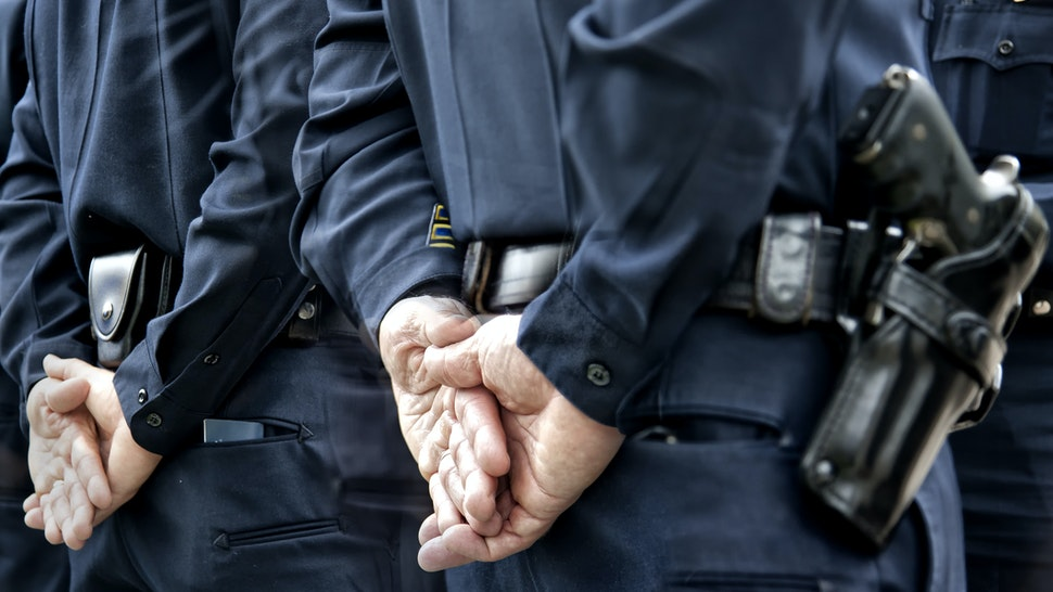 Officers standing with hands behind - stock photo