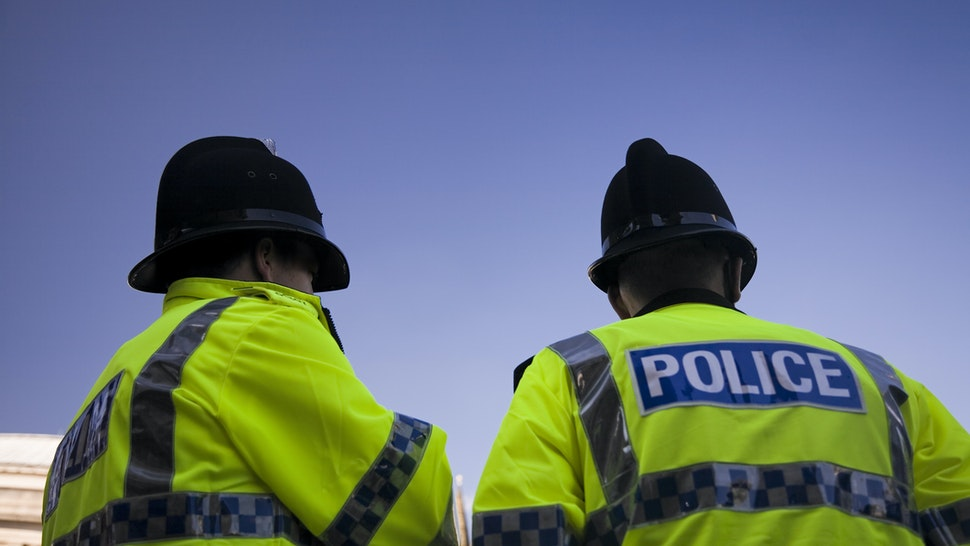 Two British Policemen wearing Traditional Helmets-Click below for more. - stock photo