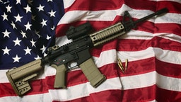 An AR-15 rifle with bullets on an American flag, a symbol of the right of patriotic Americans to bear arms, guaranteed by the Second Amendment.