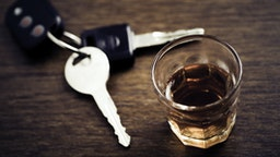A shot glass full of dark colored alcohol on top of a bar table along with a set of car keys. Drinking and driving series. Also driving under the influence of alcohol.