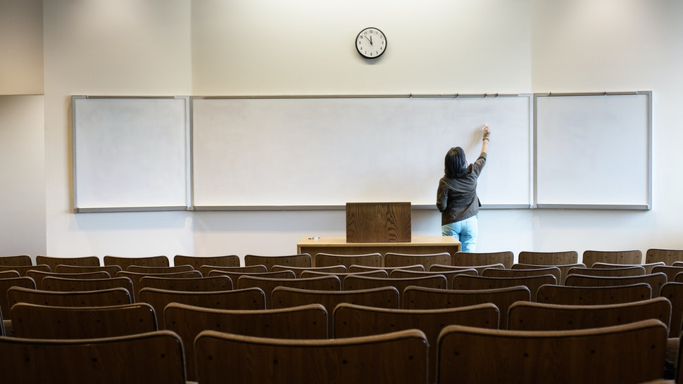 Filipino professor writing on whiteboard in empty lecture hall - stock photo