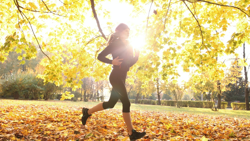 Female athlete on training run through fall leaves, city park