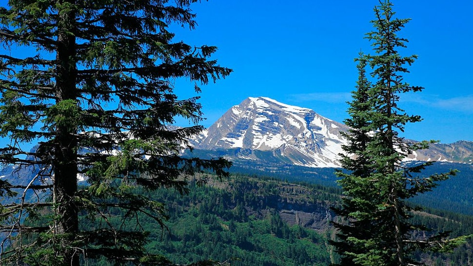 Heaven's Peak an 8987 feet elevation mountain in Glacier National Park Montana viewed from Going to the Sun Road in early summer, Heaven's Peak stands high above McDonald Creek valley on the western side of Glacier National Park.