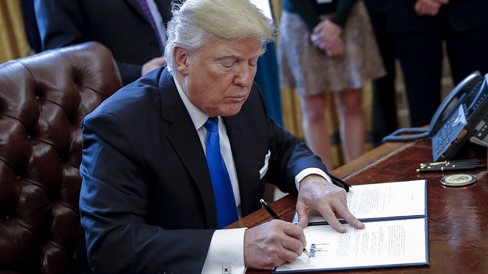 US President Donald Trump signs one of five executive orders related to the oil pipeline industry in the Oval Office of the White House in Washington, D.C., U.S., Tuesday, Jan. 24, 2017.