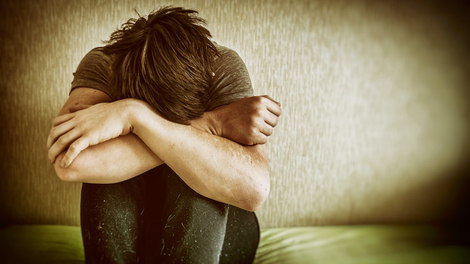 Sad Young Man Sitting On Bed At Home - stock photo