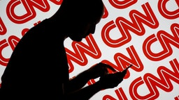 A man is seen holding with a smart device in front of a CNN logo in this photo illustration on 2 July, 2017.