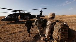 Flight medic Sgt. Aaron Burrows (C) of Amarillo, TX with C Company Dustoff 3rd Battalion of the 82nd Combat Aviation Brigade 82nd Airborne Division leads a U.S. Marine (R) and a soldier with the Afghan National Army to a MEDEVAC helicopter December 20, 2009 near Delhi, Afghanistan.