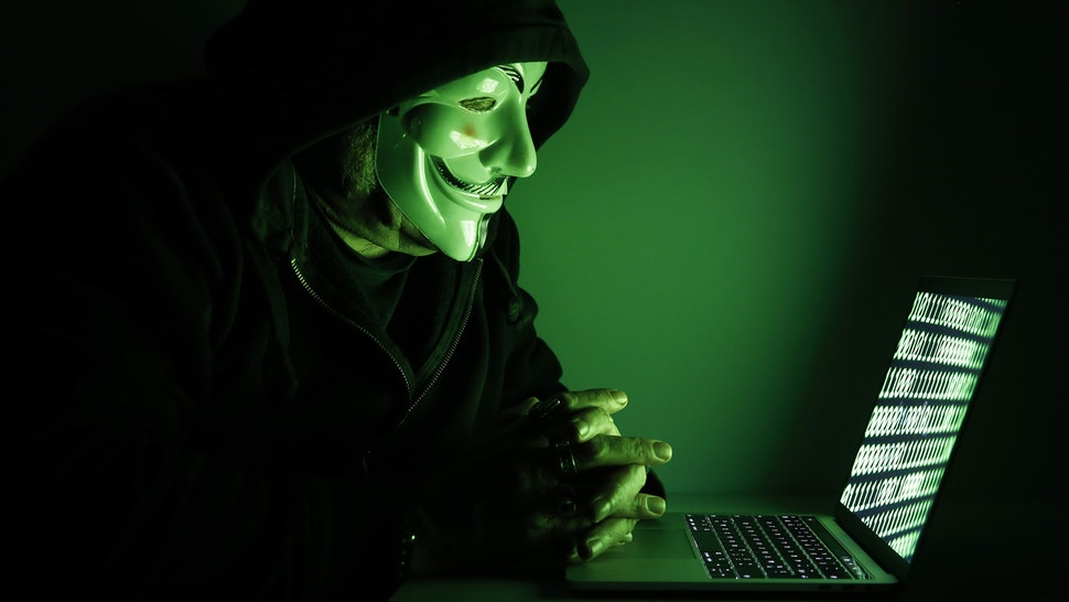 PARIS, FRANCE - DECEMBER 27: In this photo illustration, a hacker with an Anonymous mask on his face and a hood on his head uses a computer on December 27, 2019 in Paris, France. In IT security, a hacker is an IT specialist, who is looking for ways to bypass software and hardware protections. Hackers are generally intelligent programmers who seek to manipulate or modify a computer system or network.