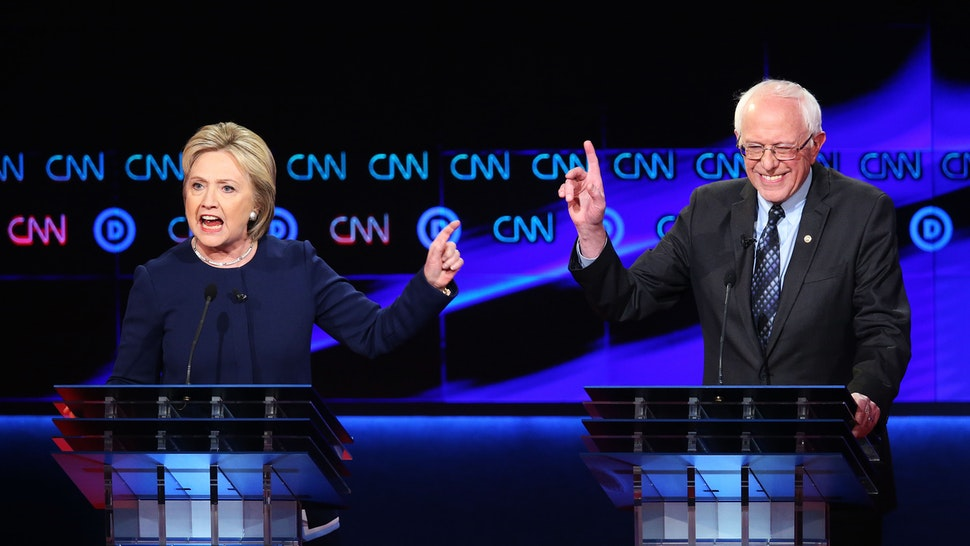 FLINT, MI - MARCH 06: Democratic presidential candidate Senator Bernie Sanders (D-VT) and Democratic presidential candidate Hillary Clinton speak during the CNN Democratic Presidential Primary Debate at the Whiting Auditorium at the Cultural Center Campus on March 6, 2016 in Flint, Michigan. Voters in Michigan will go to the polls March 8 for the state's primary.