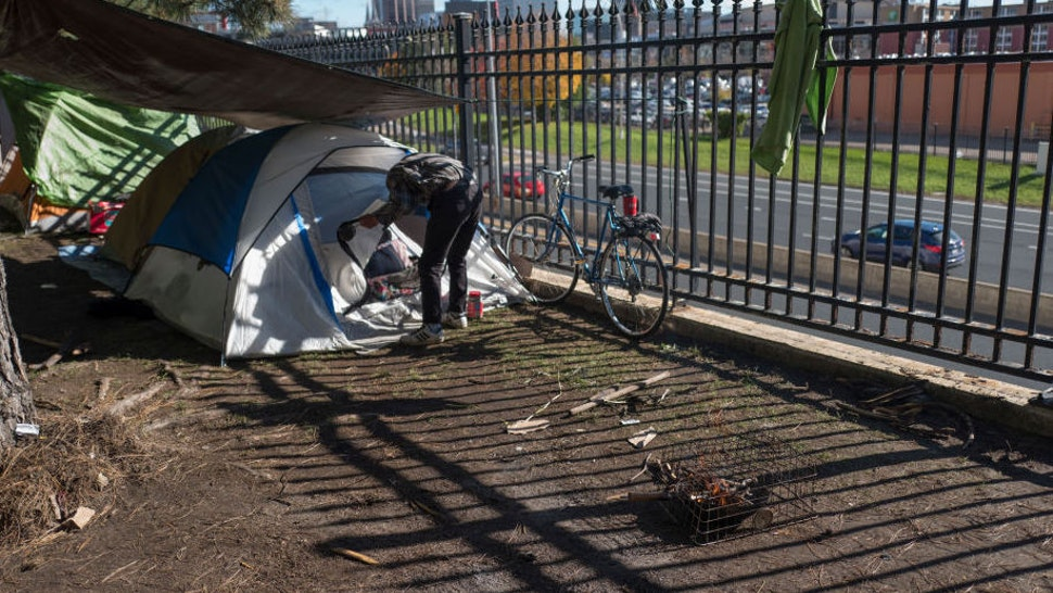 A homeless man who did not want his named used made coffee near his tent at the homeless encampment