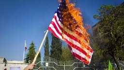 """Iranian hardline students burn a US flag during a demonstration against the Bahraini government's suppression of protests led by the mainly-Shiite opposition in the kingdom outside the Bahraini embassy in Tehran on April 15, 2011 as Iran has demanded intervention from the United Nations Security Council """"to stop the killing of the people of Bahrain""""."""