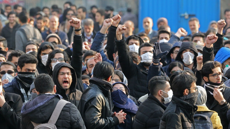 """Iranian students gather for a demonstration over the downing of a Ukrainian airliner at Tehran University on January 14, 2020. - AFP correspondents said around 200 mainly masked students gathered at Tehran University and were locked in a tense standoff with youths from the Basij militia loyal to the establishment.""""Death to Britain,"""" women clad in black chadours chanted as Basij members burned a cardboard cutout of the British ambassador to Tehran, Rob Macaire, after his brief arrest for allegedly attending a demonstration Saturday. Kept apart by security forces, the groups eventually parted ways."""