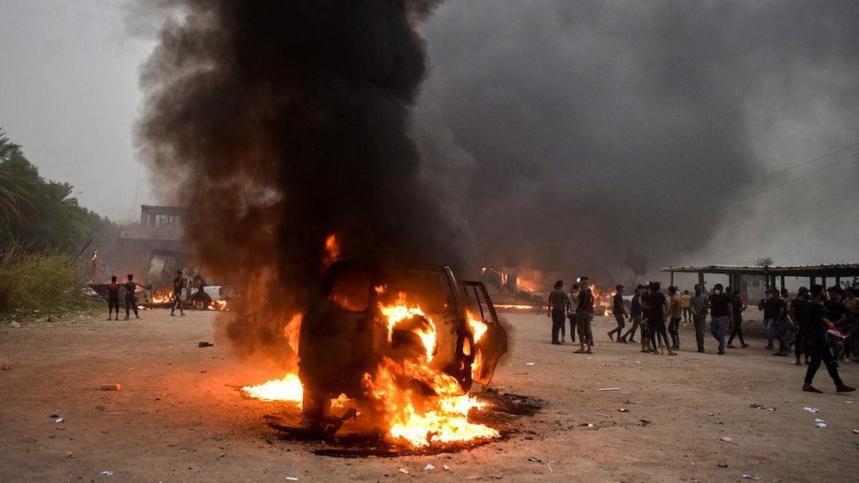 This picture taken on October 25, 2019 shows a burning car at the scene of anti-government demonstrations outside the burning local government headquarters in Nasiriyah, the capital of Iraq's southern province of Dhi Qar.