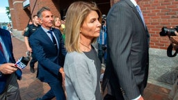 Actress Lori Loughlin (C) and husband Mossimo Giannulli (2nd L) exit the Boston Federal Court house after a pre-trial hearing with Magistrate Judge Kelley at the John Joseph Moakley US Courthouse in Boston on August 27, 2019. - Loughlin and Giannulli are charged with conspiracy to commit mail and wire fraud and conspiracy to commit money laundering in the college admissions scandal. (Photo by Joseph Prezioso / AFP) (Photo credit should rea