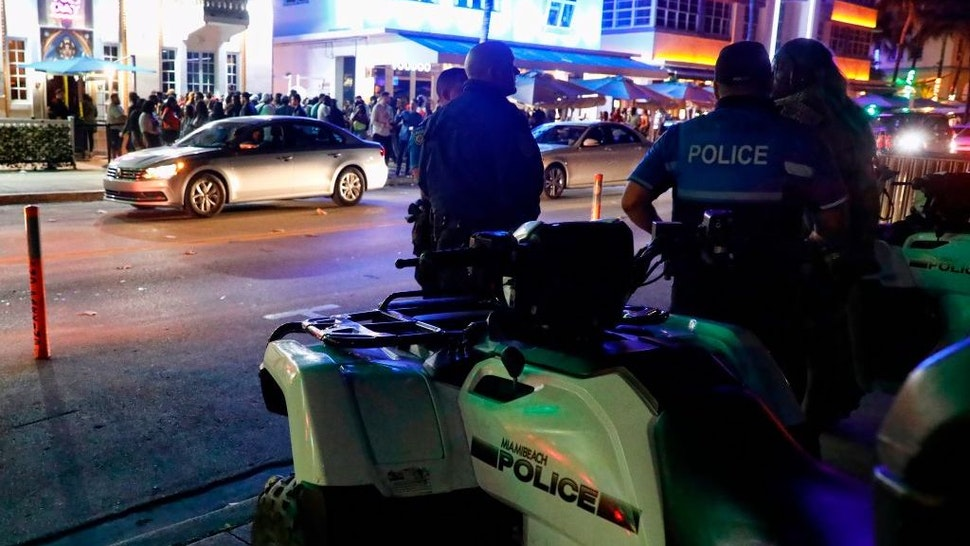 Miami Beach police officers stand across the street from the night clubs and hotels on Ocean Drive in South Beach, Florida on March 22, 2019. - The excesses of students celebrating Spring Break have reached a point that is forcing Miami Beach officials to deploy anti-riot police to quell the party. Police are also promising to stop turning a blind eye to drinking alcohol on the beach and the smoking of marijuana. (Photo by RHONA WISE / AFP)