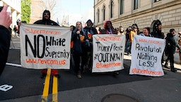 "Anti-white supremacy protesters hold banners as they shout anti-Trump slogans at the end of a rally by gun supporters outside the Virginia State Capitol grounds in Richmond, Virginia on January 20, 2020. - Several thousand gun rights supporters massed near the Virginia state capitol Monday for a rally under heavy surveillance and a state of emergency declared by authorities fearing violence by far-right groups. Dressed in hunting jackets and caps, rally-goers were checked for weapons as they passed through tight security before entering a fenced off area of Richmond's Capitol Square for the so-called ""Lobby Day"" event."