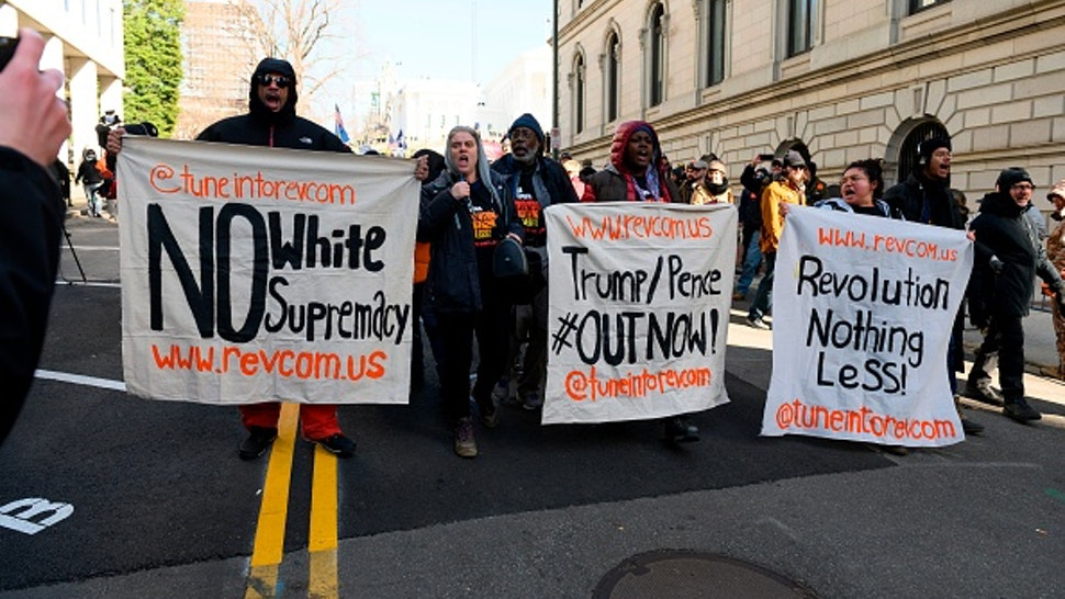 """Anti-white supremacy protesters hold banners as they shout anti-Trump slogans at the end of a rally by gun supporters outside the Virginia State Capitol grounds in Richmond, Virginia on January 20, 2020. - Several thousand gun rights supporters massed near the Virginia state capitol Monday for a rally under heavy surveillance and a state of emergency declared by authorities fearing violence by far-right groups. Dressed in hunting jackets and caps, rally-goers were checked for weapons as they passed through tight security before entering a fenced off area of Richmond's Capitol Square for the so-called """"Lobby Day"""" event."""