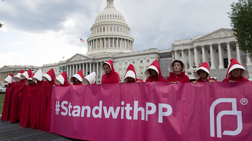 """Supporters of Planned Parenthood dressed as characters from """"The Handmaid's Tale,"""" hold a rally as they protest the US Senate Republicans' healthcare bill outside the US Capitol in Washington, DC, June 27, 2017. / AFP PHOTO / SAUL LOEB"""