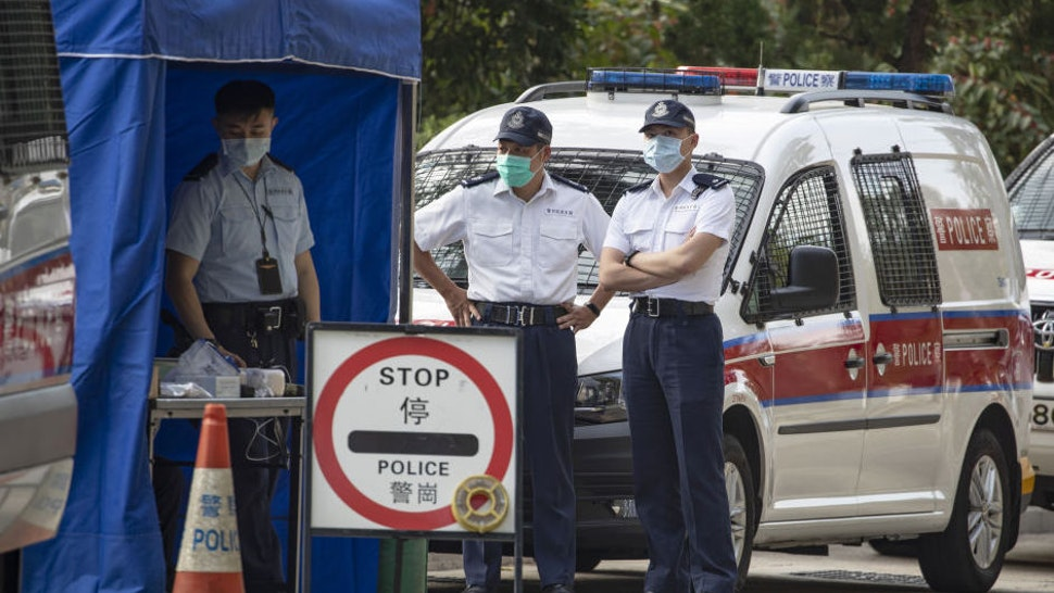 Police officers wearing face masks stand guard at a road block outside the Lady MacLehose Holiday Village, a temporary quarantine camp, in Hong Kong, China, on Thursday, Jan. 23, 2020. A deadly coronavirus, which first appeared last month in the city of Wuhan in central China, has spread from the mainland to locations from Hong Kong to the U.S., coloring what is usually a period of celebration and reunion for Chinese people across the world with tension and anxiety.
