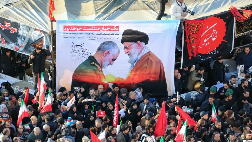 """Iranian mourners carry a picture of Iran's Supreme Leader Ayatollah Ali Khamenei (R) granting the Order of Zolfaghar, the highest military honour of Iran, to General Qasem Soleimani, during the latter's funeral procession in the capital Tehran on January 6, 2020. - Downtown Tehran was brought to a standstill as mourners flooded the Iranian capital to pay an emotional homage to Soleimani, the """"heroic"""" general who spearheaded Iran's Middle East operations as commander of the Revolutionary Guards' Quds Force and was killed in a US drone strike on January 3 near Baghdad airport along with Iraqi paramilitary chief Abu Mahdi al-Muhandis and others. (Photo by ATTA KENARE / AFP)"""
