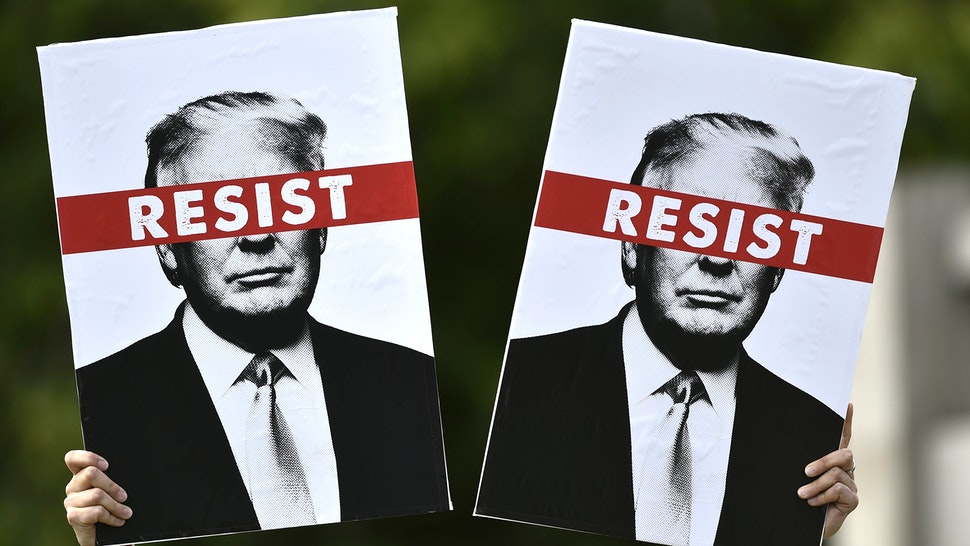 A protestor holds placards prior to the Scotland United Against Trump march through the streets of Edinburgh, Scotland on July 14, 2018, on the third day of US President Donald Trump's four-day UK visit. - US President Donald Trump wraps up a four-day visit to Britain, dominated by his blasting of Prime Minister Theresa May's Brexit strategy, by spending the weekend in Scotland.