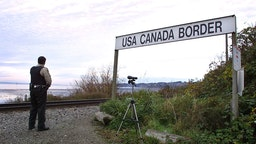 A Canadian Customs and Fisheries officer watches over the U.S.-Canada border between Blaine, Washington and White Rock, British Columbia November 8, 2001 in White Rock, BC. The Peace Arch border crossing is one of the busiest crossings in North America. (Photo by Jeff Vinnick/Getty Images)