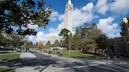 Berkeley California University of California at Berkeley, students with Sather Tower or Campanile tower in background with clouds and color.