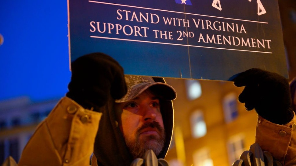 A protestor holds a sign in front of the Virginia State Capitol building in Richmond, Virginia on January 20, 2020. - Thousands of gun rights supporters descended for a rally in the grounds of the State Capitol under heavy surveillance after authorities were forced to declare a state of emergency for fear of violence by far-right groups. (Photo by Roberto SCHMIDT / AFP)