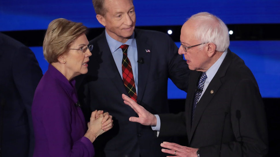 Sen. Elizabeth Warren (D-MA) and Sen. Bernie Sanders (I-VT) speak as Tom Steyer looks on after the Democratic presidential primary debate at Drake University on January 14, 2020 in Des Moines, Iowa. Six candidates out of the field qualified for the first Democratic presidential primary debate of 2020, hosted by CNN and the Des Moines Register. (Photo by Scott Olson/Getty Images)