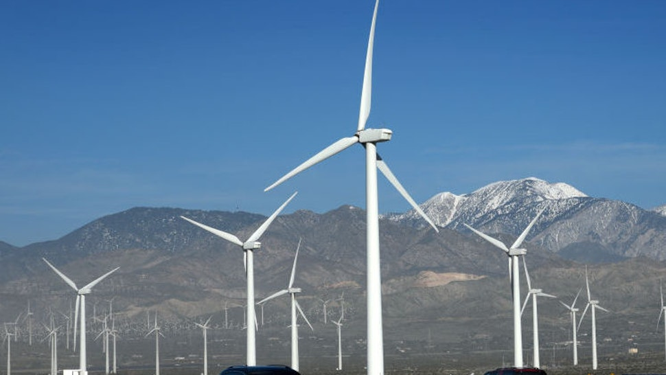PALM SPRINGS, CALIFORNIA - FEBRUARY 27, 2019: Automobiles travel along Interstate 10 as wind turbines generate electricity at the San Gorgonio Pass Wind Farm near Palm Springs, California. Located in the windy gap between Southern California's two highest mountains, the facility is one of three major wind farms in California.