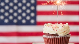 A cupcake stands in front of an American flag