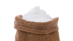 Close-Up Of Monosodium Glutamate In Sack Against White Background