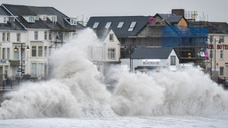 Huge waves hit the sea wall in Porthcawl, Wales, as gales of up to 80mph from Storm Brendan caused disruption around the UK.