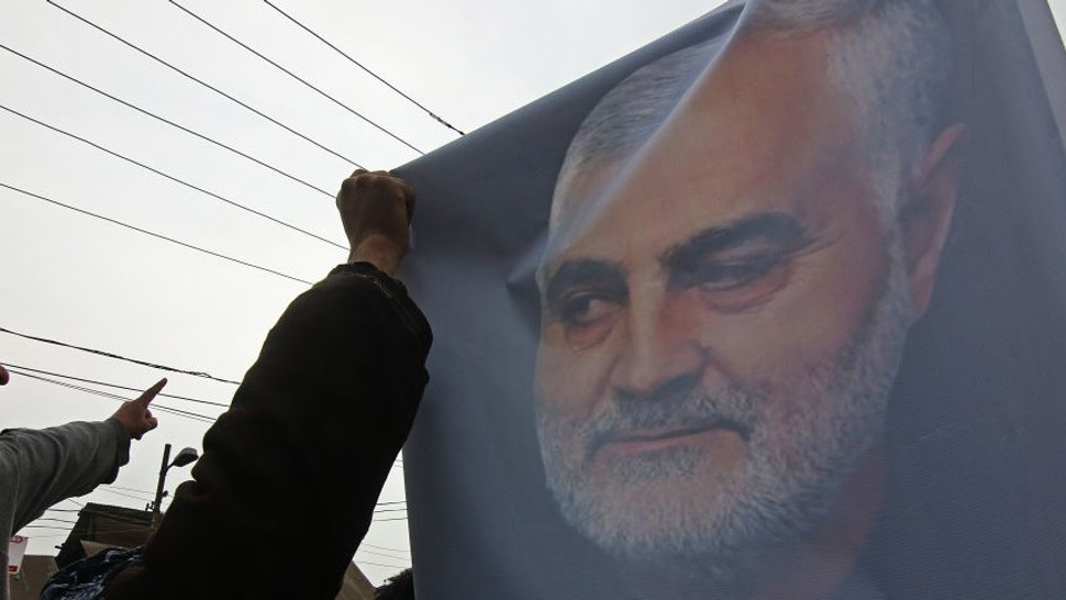 A Kashmiri Shiite muslim holds a picture of Iranian military General Qassem Soleimani as he marches during an anti-America protest in central Kashmir on January 03, 2020.The agitated protesters were chanting anti-America slogans and staged a protest against the killing of Soleimani by a US air strike in Baghdad.
