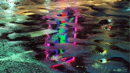 The bright lights of the Ginza district of Tokyo, reflected in a wet road surface, Japan, June 1984.
