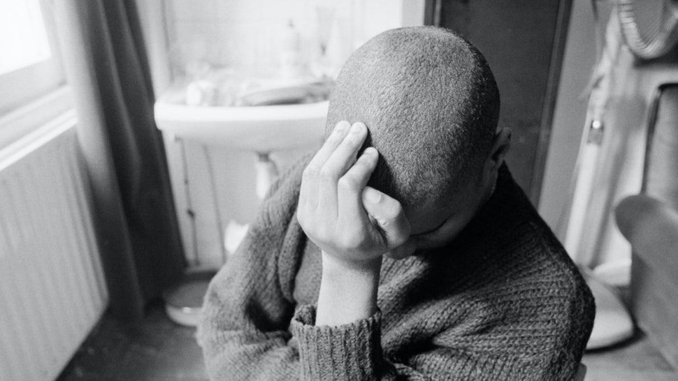 A man sitting alone in a room, leaning his head against the heel of his hand, circa 1985.