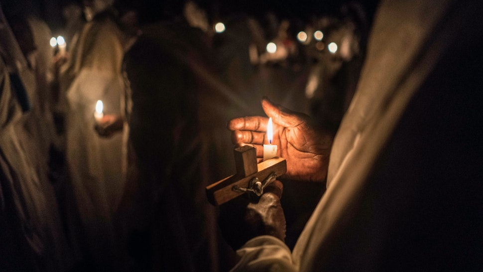 Believers of Legio Maria of African Church Mission hold candles during their overnight Christmas Mass at the church near Ugunja, the western part of Kenya, early December 25, 2017.
