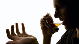 Depressed young man with some sleeping pills and glass of whiskey.