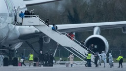 BRIZE NORTON, ENGLAND - FEBRUARY 9: People in protective suits assist passengers as they disembark from a plane, carrying 150 Britons who were trapped in Wuhan following a Coronavirus outbreak, after landing at RAF Brize Norton from China on February 9, 2020 in Brize Norton, England. British citizens who arrived from Wuhan on two previous repatriation flights from Wuhan are quarantined at Arrowe Park Hospital on the Wirral. Coronavirus started in Wuhan in the Hubei Province of China and has spread to two dozen countries worldwide with three confirmed cases in the UK.