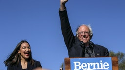NEW YORK, NY - OCTOBER 19: Democratic presidential candidate, Sen. Bernie Sanders (I-VT) waves with Rep. Alexandria Ocasio-Cortez (D-NY) as she endorses him during his speech at a campaign rally in Queensbridge Park on October 19, 2019 in the Queens borough of New York City. This is Sanders' first rally since he paused his campaign for the nomination due to health problems.