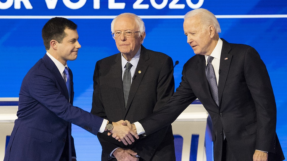 Pete Buttigieg, former mayor of South Bend and 2020 presidential candidate, left, shakes hands with Former Vice President Joe Biden, as Senator Bernie Sanders, an Independent from Vermont, stands on stage ahead of the Democratic presidential debate at Saint Anselm College in Manchester, New Hampshire, U.S., on Friday, Feb. 7, 2020. The New Hampshire debates often mark a turning point in a presidential campaign, as the field of candidates is winnowed and voters begin to pay closer attention.