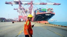 A Chinese worker looks on as a cargo ship is loaded at a port in Qingdao, eastern China's Shandong province on July 13, 2017. China's exports rose a forecast-beating 11.3 percent on-year in June, data showed July 13, fuelling hopes of stability in the world's second-largest economy.
