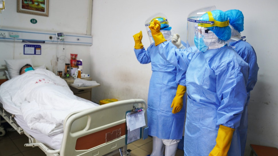 This photo taken on January 28, 2020 shows medical staff members cheering up a patient infected by the novel coronavirus in an isolation ward at a hospital in Zouping in China's easter Shandong province. - China faced deepening isolation over its coronavirus epidemic on February 1 as the death toll soared to 259, with the United States leading a growing list of nations to impose extraordinary Chinese travel bans.