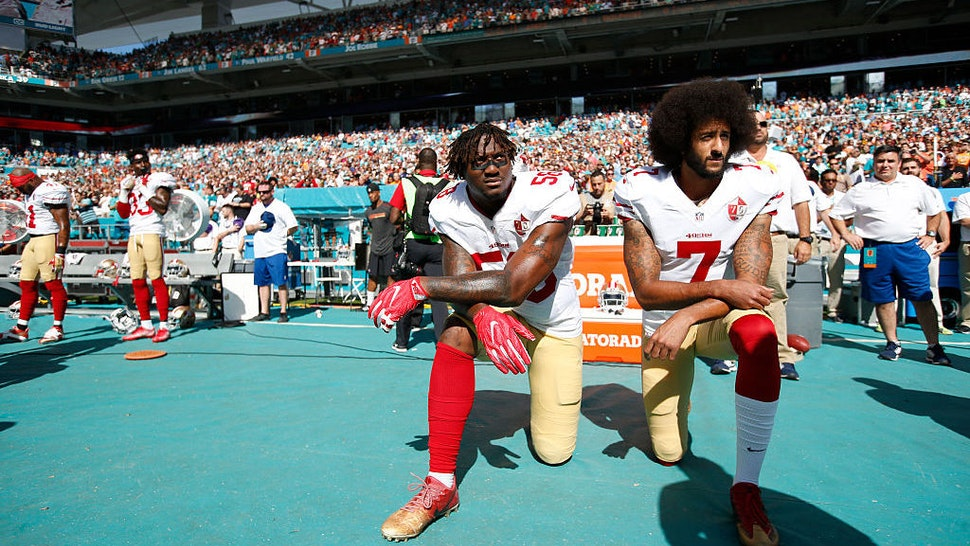 Eli Harold #58 and Colin Kaepernick #7 of the San Francisco 49ers kneel on the sideline, during the anthem, prior to the game against the Miami Dolphins at Hard Rock Stadium on November 27, 2016 in Miami Gardens, Florida. The Dolphins defeated the 49ers 31-24. (Photo by Michael Zagaris/San Francisco 49ers/Getty Images)