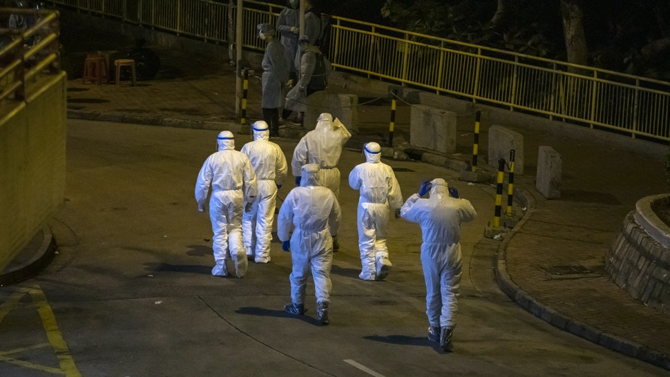 Officials wearing protective gear walk through Cheung Hong Estate in the Tsing Yi district of Hong Kong, China, in the early morning of Tuesday, Feb. 11, 2020. The Hong Kong government has evacuated some residents at a building where two patients have been confirmed to have the coronavirus infection, according to Wong Ka-Hing, controller at the Centre for Health Protection.